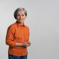 Cheerful woman with gray hair smiles against an isolated background. Woman wearing orange shirt posing in studio. High quality photo