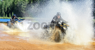 Two Men driving motocross ATV quad through splashing river lake water with high speed. Foy, Foyross Lake, Sudbury, Canada.