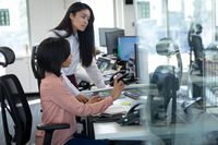 Two businesswomen working together at modern office