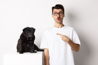 Happy young man showing his cute dog, pointing finger at black pug and staring amazed, standing over white background