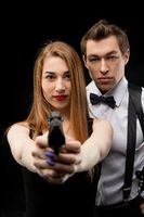 Young sexy couple with gun aim at camera