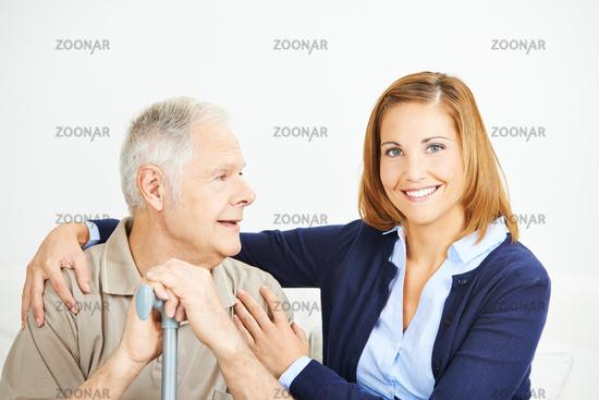 Lächelnde Frau umarmt Senior im Seniorenheim