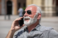 Old man use internet application on smartphone, seating on bench,  stock photo