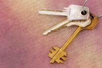 Three old house keys on keyring over grunge backgr