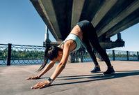 Young sporty woman doing yoga asana downward facing dog under industrial bridge