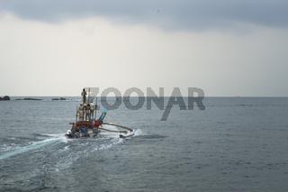 Mirissa, Sri Lanka - April 9 2017: Local fisherman sailing to the open sea at sunrise