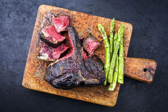 Barbecue dry aged wagyu bistecca alla fiorentina beef steak sliced with large filet piece with green asparagus and red wine salt offered as top view on an old rustic wooden cutting board
