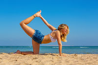 Young european woman in yoga position on beach