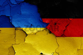flags of Ukraine and Germany painted on cracked wall