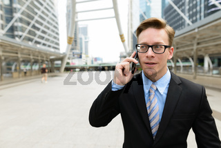 Young handsome blond businessman talking on the phone in the city outdoors