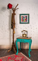 Wooden vintage side table, golden antique telephone, and coat hanger stand with red fez and scarf