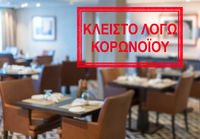 Modern restaurant with tables closed and sign in Greek saying Closed due to Coronavirus