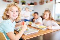 Kinder essen in Kantine einer Grundschule Mittagessen