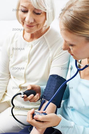 Frau beim Blutdruck messen von Seniorin