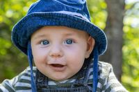 Laughing baby enjoying with father in garden