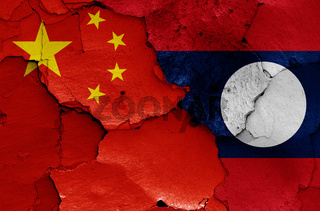 flags of China and Laos painted on cracked wall