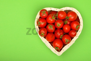 Cherry tomatoes in heart shaped basket on green