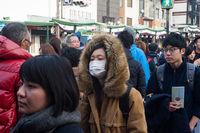 Kyoto, Japan, Frau mit Mundschutz in einer Menschenmenge im Stadtzentrum