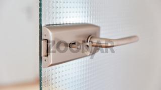 Tür aus Glas mit Türklinke und Schlüssel im Schloss