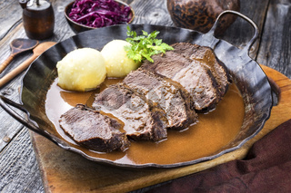 Traditional braised marinated German Sauerbraten from beef with potato dumplings and blue kraut in spicy brown sauce as closeup in a rustic wrought iron pan