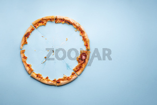 Pizza crust leftovers on blue paper background, top view