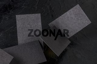 Thick black business cards, floating on a black background, a mockup