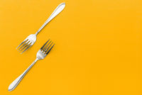 Stainless steel cutlery on a colored background. Two silver forks for food. Cooking utensils. Restaurant menu concept.