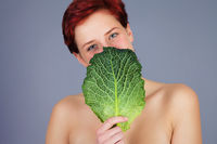 woman hiding behind savoy cabbage leaf