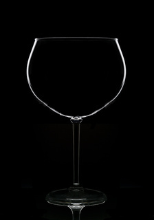 An empty wine glass in silhouette with reflection, isolated on black.