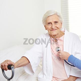 Seniorin wird mit Stethoskop abgehört