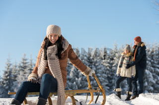 Young people enjoy sunny winter snow sledge