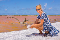 Woman holding white foam  near orange salt lake