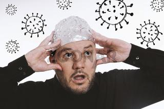 paranoid man wearing tin foil hat against corona virus covid-19