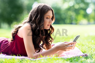 beautiful young woman with smartphone at park