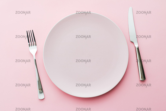 Empty plate and cutlery as mockup set on pink background, top tableware for chef table decor and menu branding