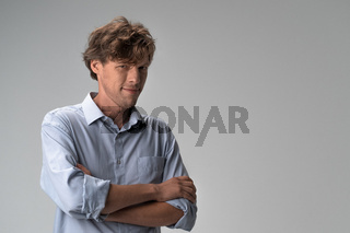 Positive man looks confidently with his arms crossed