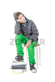 sad male sitting  teenager with one foot on a stack of books, isolated on white