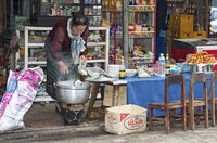 Local woman draws soup into a bag at a small food stall, Luang Prabang, Laos