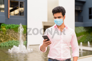 Young Indian businessman with mask using phone in the city outdoors