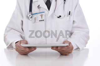Closeup of a doctor holding a tablet computer as he sits at his desk. Focus is on Tablet, ID TAGis computer generated.