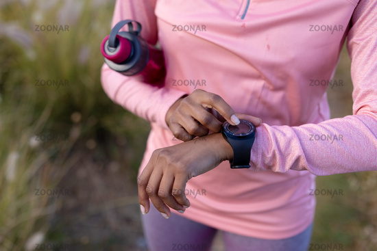 Portrait of fit african american woman in sportswear using smartwatch holding water in tall grass