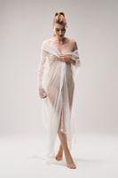 Tender naked woman in white veil in studio