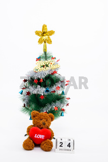Decorated Christmas tree with Merry Christmas writing and teddy bear holding heart beside 24 December calendar