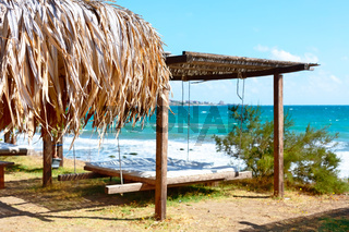 Umbrella and beach bed with lounge, sea and blue sky