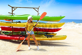 Young woman near kayaks at sunny day