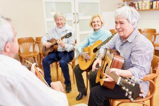 Gruppe Senioren nimmt Gitarrenunterricht in der Volkshochschule