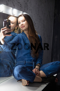 Charming woman dressed in denim overalls