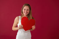 Smiling woman holding papper heart in hands on red background