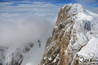 Snowy alpine mountainside with clouds
