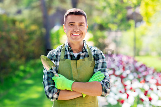 happy man in apron with scoop at summer garden